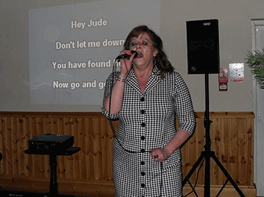 Wedding karaoke with a lady singing at Muncaster Castle.